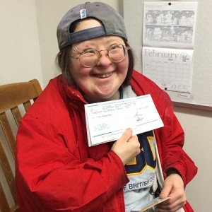 Teresa holds her DTES arts grant cheque with pride