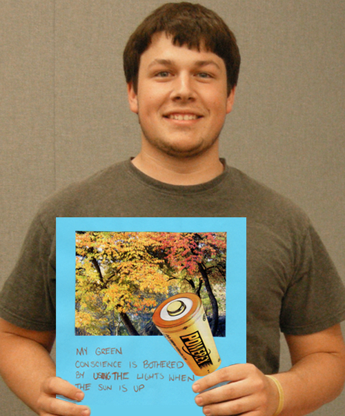 University of Cincinnati student holds up his Green Conscience art work