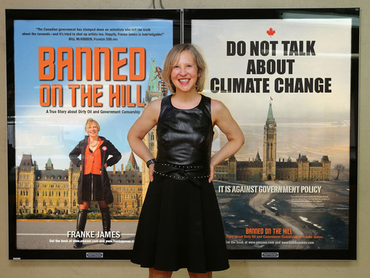 Franke James in Halifax in front of two of her posters, photo by Nick Pearce